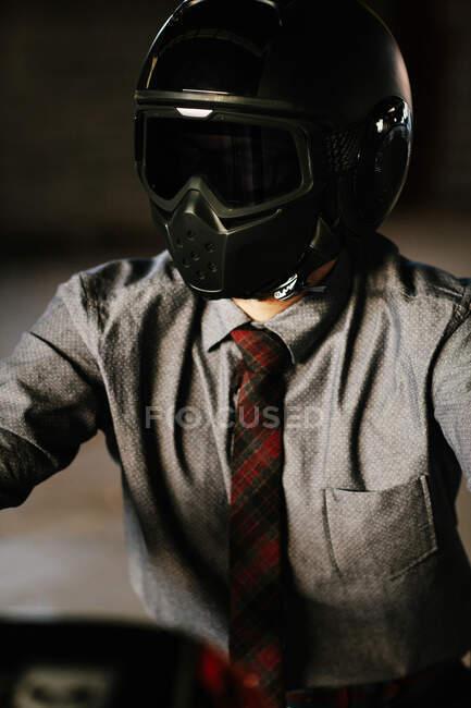 Элегантный мужчина сидит на своем красивом мотоцикле в гараже — стоковое фото