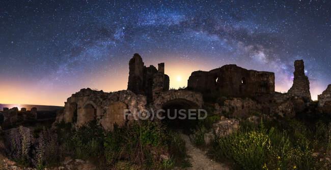 Чудесні краєвиди зруйнованого стародавнього палацу під Чумацьким Шляхом у зоряному небі вночі. — стокове фото