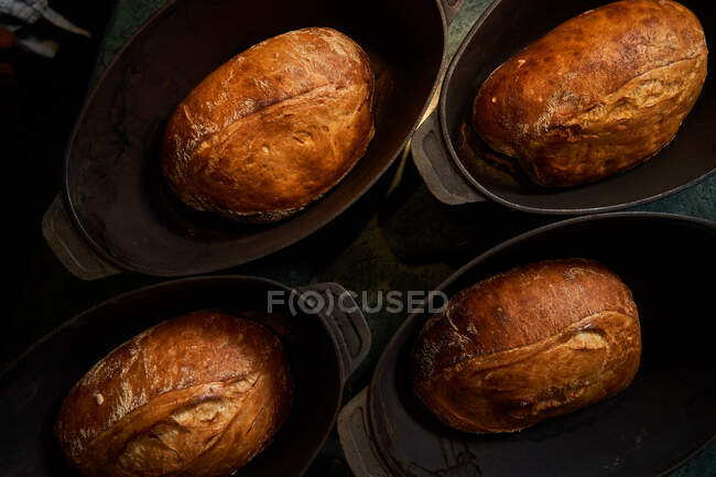 Top view of cooked golden bread loaves in cast iron forms on table — Stock Photo