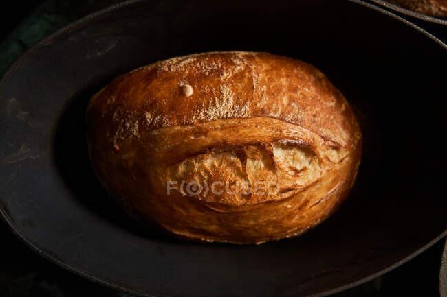 Vista superior de los panes dorados cocidos en formas de hierro fundido sobre la mesa - foto de stock