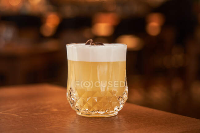 Glass of classic alcohol cocktail Whiskey Sour with lemon juice and egg white placed on wooden counter — Stock Photo