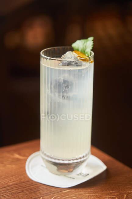 Cocktail de vodka et d'alcool tonique en verre highball décoré de feuilles de glace et de menthe sur fond sombre — Photo de stock