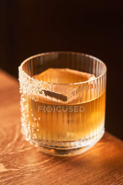 Short glass of amber alcohol whiskey cocktail with ice decorated with sugar placed on wooden counter with black background — Fotografia de Stock