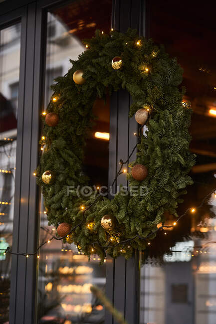 Facade of cafe with colorful decorations of coniferous branches and Christmas tree with garlands in daylight — Stock Photo