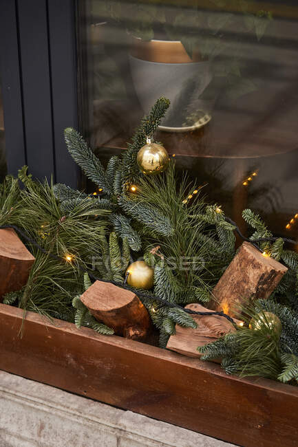 From above of decoration with firewood and coniferous branches with baubles on outside sill of cafe — Stock Photo