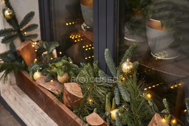 Du dessus de la décoration avec du bois de chauffage et des branches de conifères avec des boules sur le seuil extérieur du café — Photo de stock