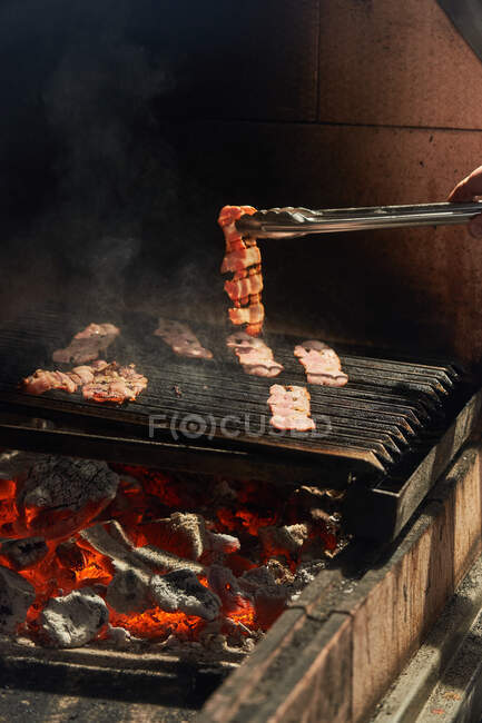 Crop chef turning straps of grilling juicy bacon while cooking with smoke on rack in garden — Stock Photo