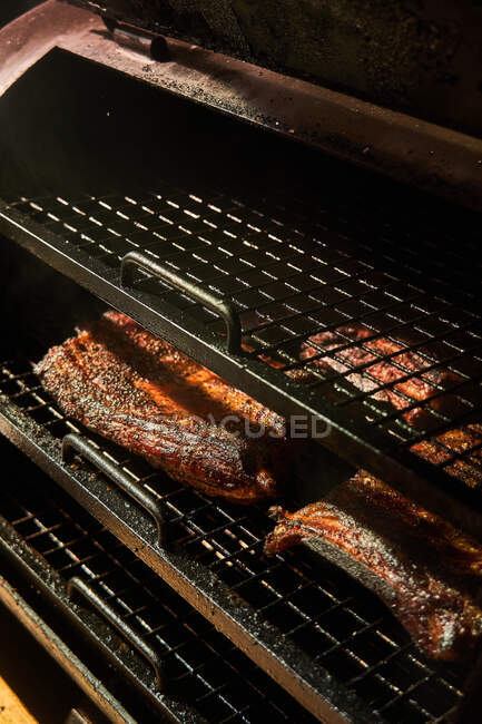 From above of smoking slices of meat on grill rack in barbecue — Stock Photo