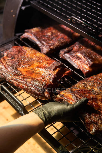 From above of crop chef in gloves grilling chunks of meat in on rack in barbecue — Stock Photo