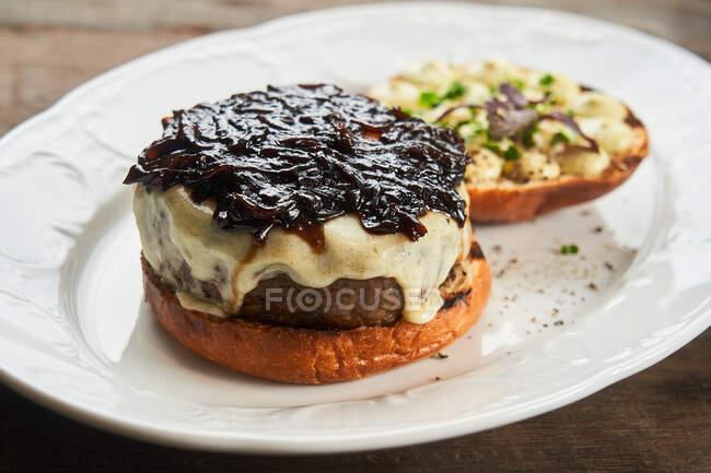 Von oben leckerer offener Rindfleisch-Burger mit Käse und BBQ-Sauce auf dem Teller auf dem Tisch — Stockfoto
