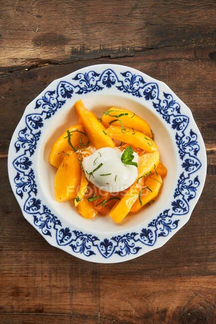 Dall'alto deliziosi pezzi di zucca preparati luminosi con uovo in camicia decorato con verdure sul piatto su tavolo di legno rustico — Foto stock