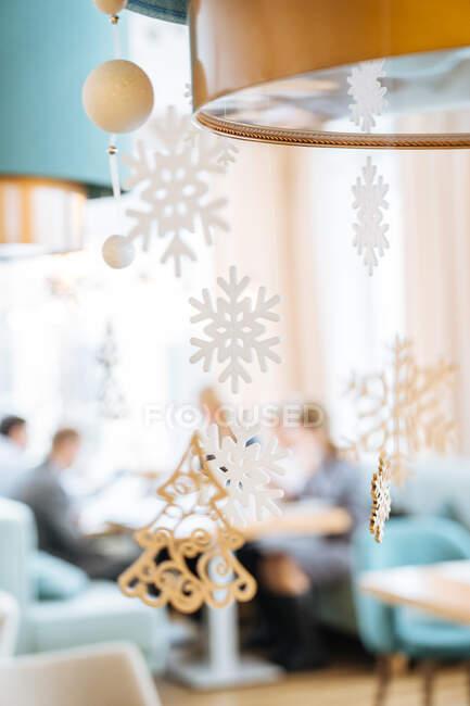 Accogliente caffè decorato con fiocchi di neve appesi bianchi e abete durante le vacanze di Natale — Foto stock
