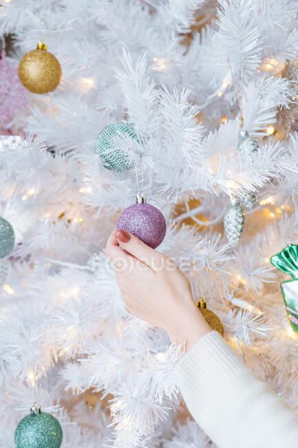 Décorations de Noël suspendues féminines sans visage sur sapin blanc artificiel à la maison — Photo de stock