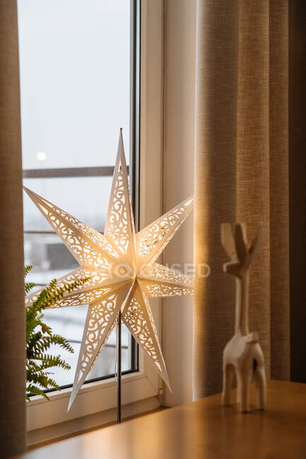 Decorative star shape lamp at window and wooden souvenir on table at home — Stock Photo