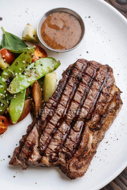 Desde arriba vista superior del filete de ternera a la parrilla con albahaca y verdura servido en el plato con salsa barbacoa - foto de stock