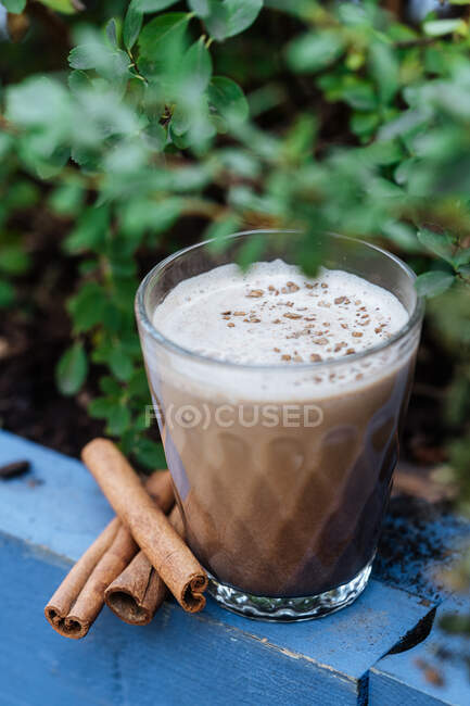 From above refreshment beverage eggnog with cinnamon in glass cup on rustic surface — Stock Photo