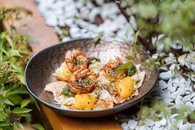 De arriba los huevos sabrosos fritos frescos con los langostinos cubiertos por las hierbas en la cacerola sobre la mesa de madera en el jardín - foto de stock