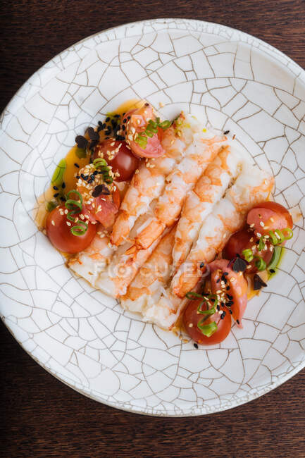From above tasty shrimps with red sliced tomatoes sprinkled with sesame seeds and herbs on white decorative plate — стоковое фото