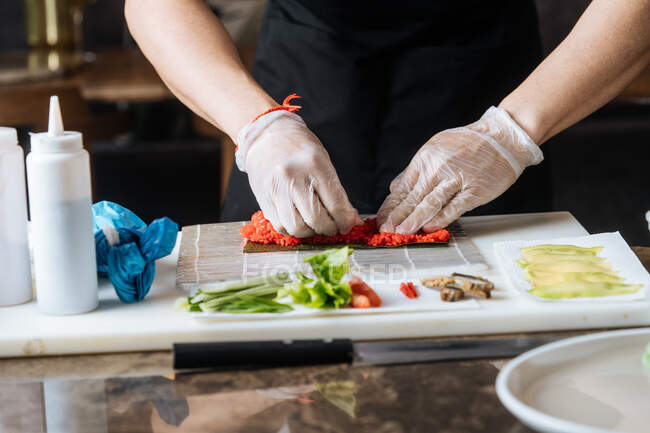 Crop qualified cook in disposable gloves kneading red spicy stuffing on table with greens fish and sauces in kitchen - foto de stock