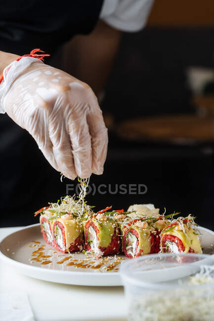 Crop cook in disposable gloves decorating fresh tasty sushi with greens on white plate on table - foto de stock