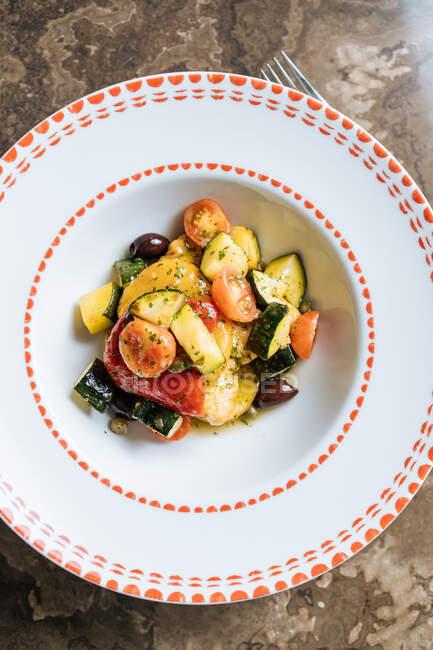 De arriba jugosa ensalada de hortalizas frescas del tomate la zanahoria de coliflor con verde en el plato blanco ornamental sobre la mesa redonda en el restaurante - foto de stock