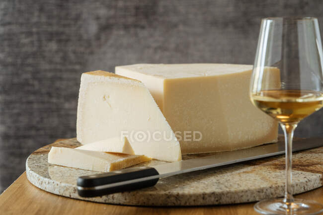 Gourmet appetizing block of cheese knife on cutting board and wine in glass on table — Stock Photo