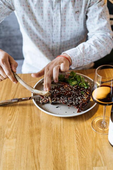Земледелец режет сочные аппетитные говяжьи ребрышки вилкой и ножом в тарелке с зеленым гарниром за столом и пьет вино в ресторане — стоковое фото