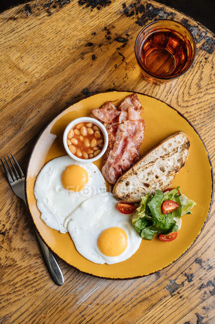 From above appetizing fried eggs bacon corn in tomato greens on yellow plate in with drink in cafe — Stock Photo