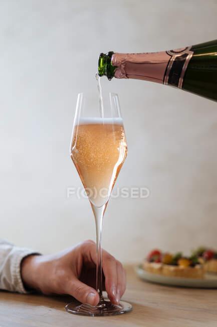 Клич тримає скло і чекає, поки розсадник наливає алкоголь в ресторані. — стокове фото