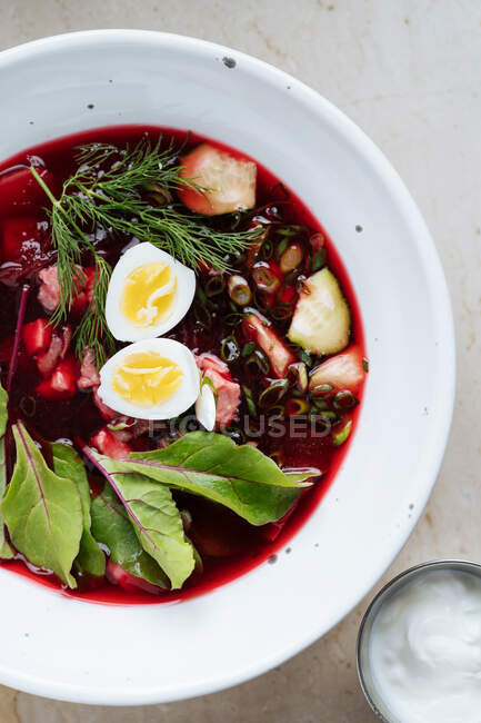 From above palatable red beetroot soup with boiled eggs and herbs in white plate on table — Stock Photo