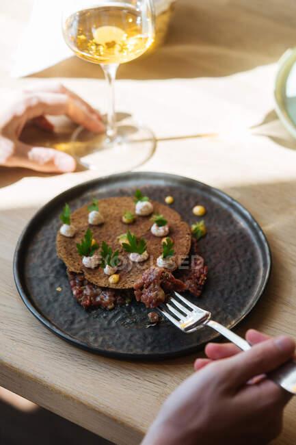 De arriba el hombre de la cosecha que come la avena sabrosa adornada con hierbas y garbanzos en el plato servido con vino en la mesa - foto de stock