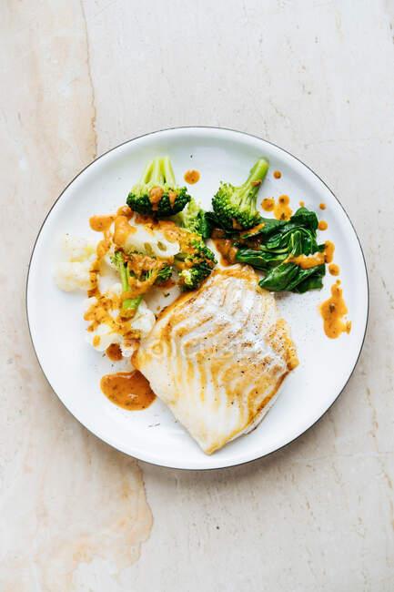 Вид свіжої риби з зеленою і брокколі посипаний червоним соусом на білій тарілці. — стокове фото