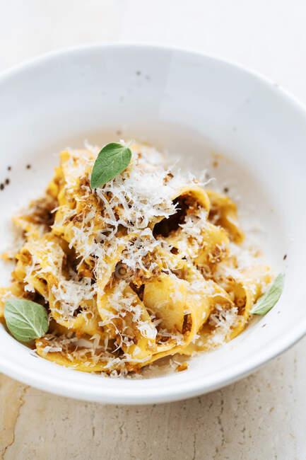 Dall'alto di piatto saporito con pasta larga cosparsa di formaggio e decorata con menta fresca in ristorante — Foto stock