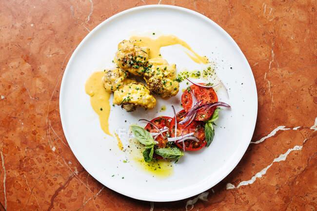 Vista dall'alto di pezzi di carne arrotondati in salsa gialla ed erbe aromatiche su piatto bianco con fette di menta di pomodoro e cipolla rossa nel ristorante — Foto stock