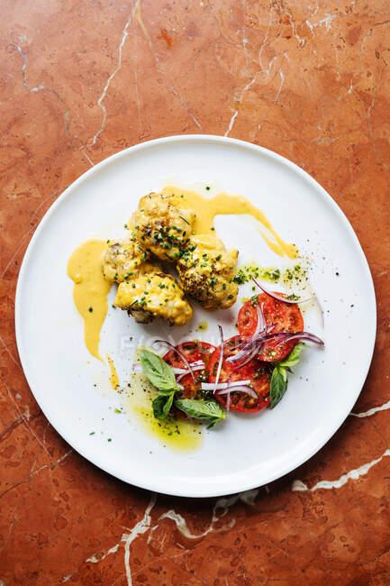 Vista superior de trozos redondeados de carne en salsa amarilla y hierbas en plato blanco con rodajas de menta de tomate y cebolla roja en el restaurante - foto de stock
