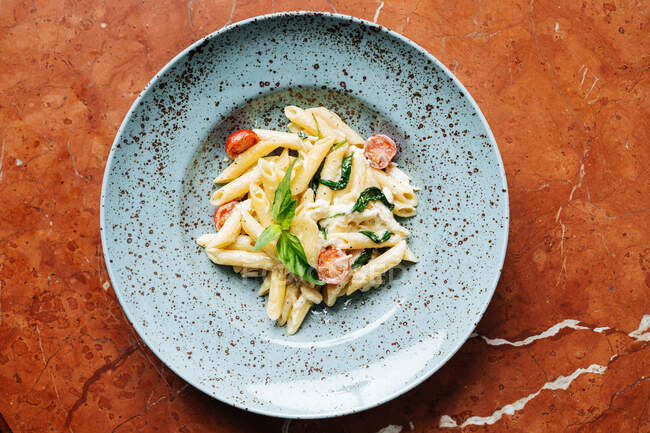 Top view of stylish plate with delicious pasta pieces of cherry tomatoes and greenery in restaurant — Stock Photo