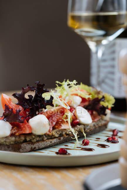 Вкусный ржаной хлеб с соусом и подается с ломтиками помидоров красочный салат и сыр на столе с бокалом вина в ресторане — стоковое фото