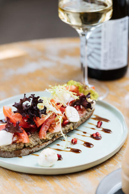 Delicioso pan de centeno untado con salsa y servido con rebanadas de tomates lechuga colorida y queso en la mesa con copa de vino en el restaurante - foto de stock