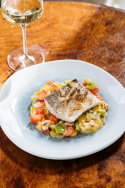 Von oben Filetfisch mit kleinen quadratischen Paprikascheiben auf dem Teller im Restaurant — Stockfoto