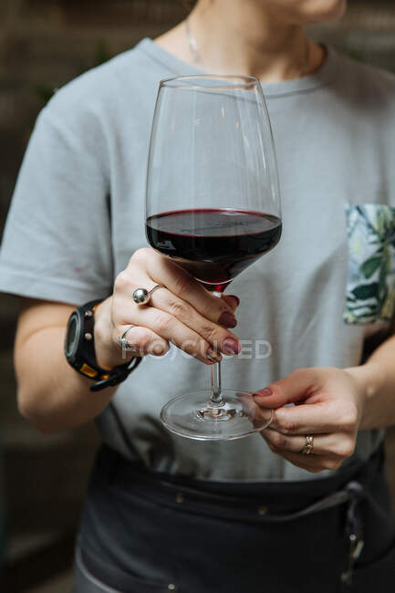 From below of crop unrecognizable female hand with stylish glass of red wine — стоковое фото