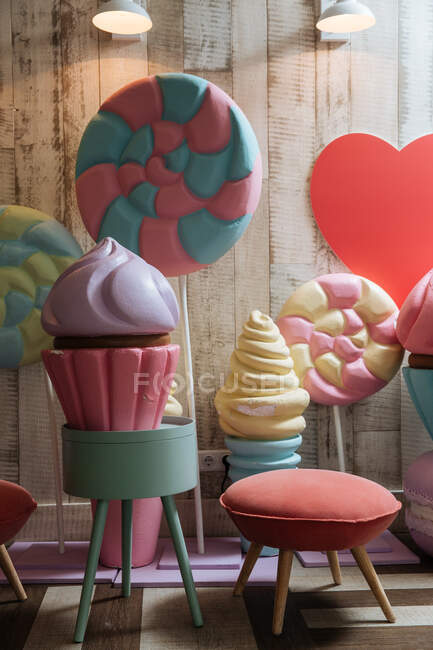 Colorful plastic ice cream cakes and candies near soft small chair in modern children room — стоковое фото