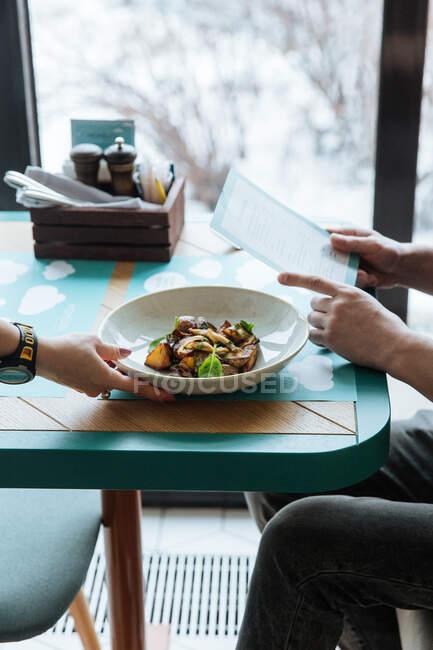 Сверху кукурузная рука официанта накрывает стол блюдом высокой кухни, а анонимный гость читает меню в современном ресторане — стоковое фото