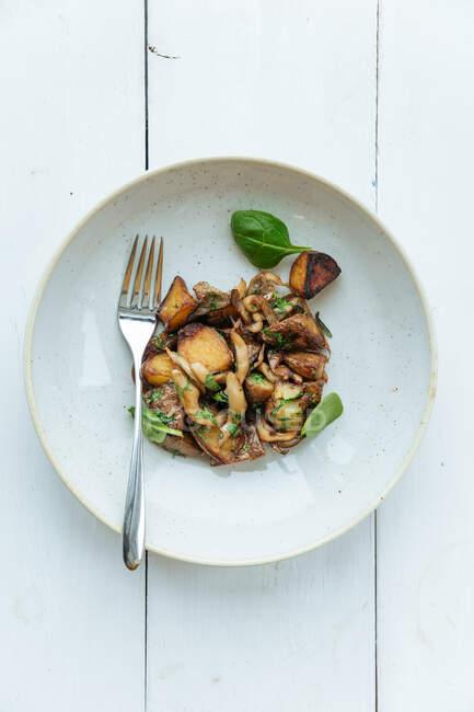 Dall'alto cucina alta piatto vegetariano con patate dolci decorate con foglie di basilico fresco sul tavolo di legno withe — Foto stock