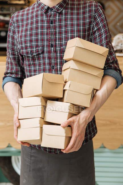 Homme méconnaissable en chemise à carreaux tenant beaucoup de petites boîtes en carton avec de la nourriture livrée au restaurant — Photo de stock
