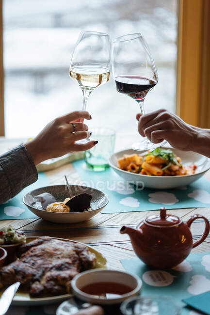 Crop male and female hands with glasses and white and red wines toasting during dinner in modern restaurant — Stock Photo