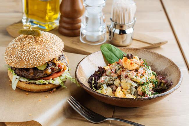 Hamburguesa grande sobre papel con queso chuleta y verduras servida con tazón de ensalada colorida en restaurante moderno - foto de stock