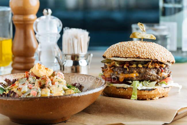 Большой гамбургер на бумаге с котлетным сыром и овощами подается с миской красочного салата в современном ресторане — стоковое фото