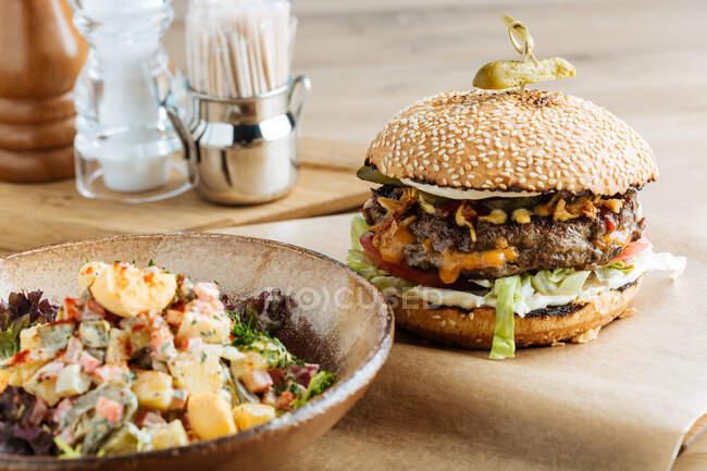 Hambúrguer grande em papel com queijo de costeleta e legumes servidos com tigela de salada colorida no restaurante moderno — Fotografia de Stock