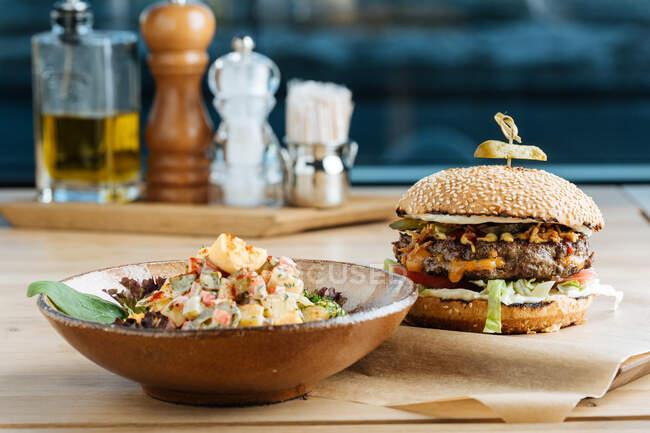Великий гамбургер на папері з сиром і овочами подається з мискою барвистого салату в сучасному ресторані. — стокове фото