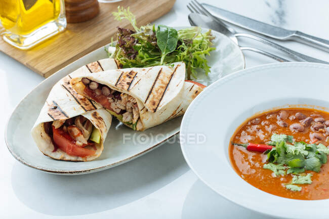 De arriba de la sopa con los frijoles el perejil fresco y los giroscopios con hortalizas y la carne a la mesa en el restaurante - foto de stock
